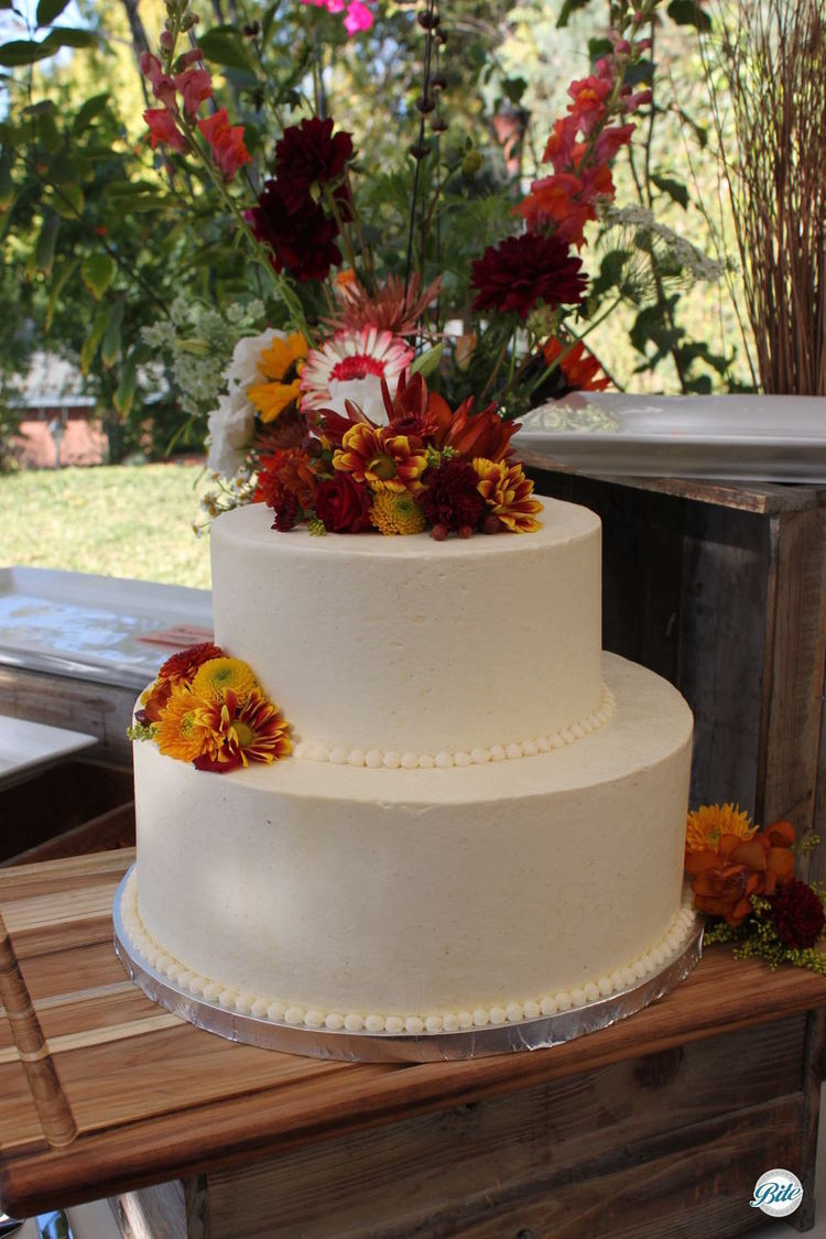 Wedding cake decorated with flowers colored for the fall. Overlooking the backyard
