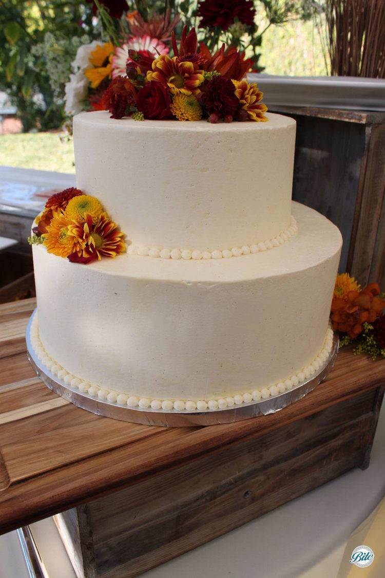 Closeup of white wedding cake with fall-colored floral and pearls