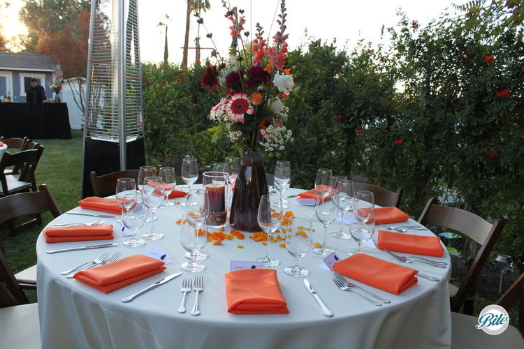 Table set with orange for the fall.  In the backyard.