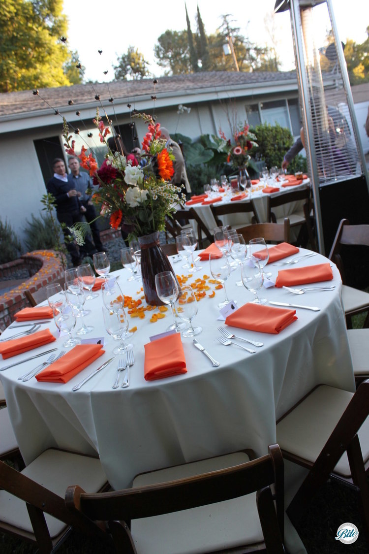 Backyard wedding reception.  Seating outdoors in the yard with a view to the house.