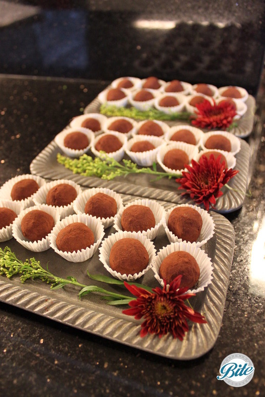 Truffles prepared for passed service with floral garnish on tray