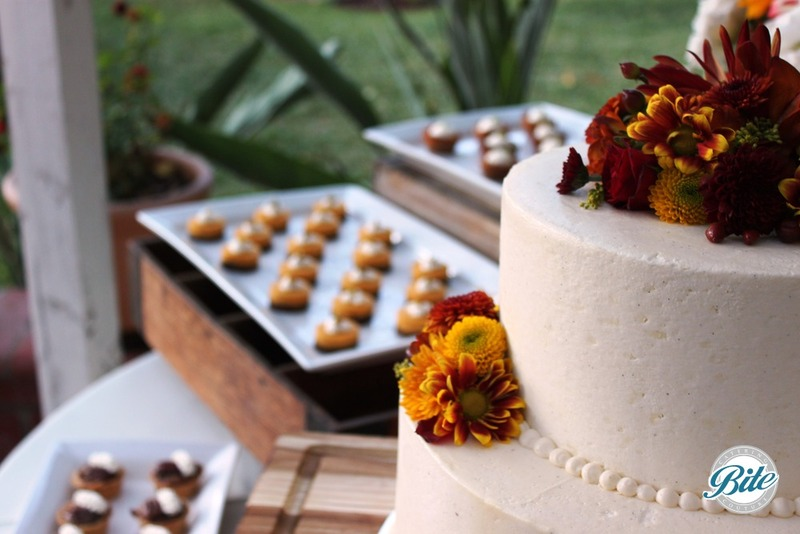 Side view of wedding cake overlooking dessert display