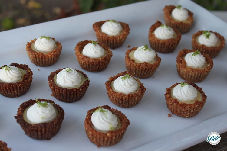 Cashew crusted Key Lime Pies. Arranged on white display tray.