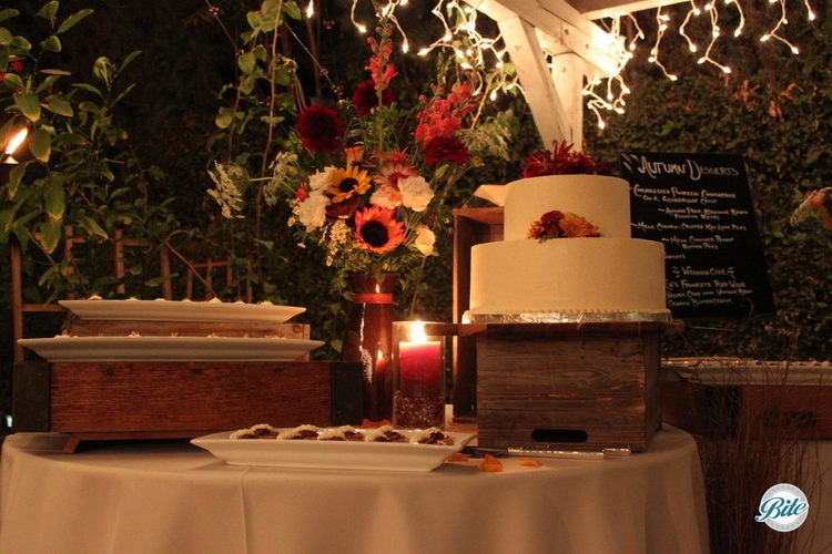 View of the dessert station and cake under the lights