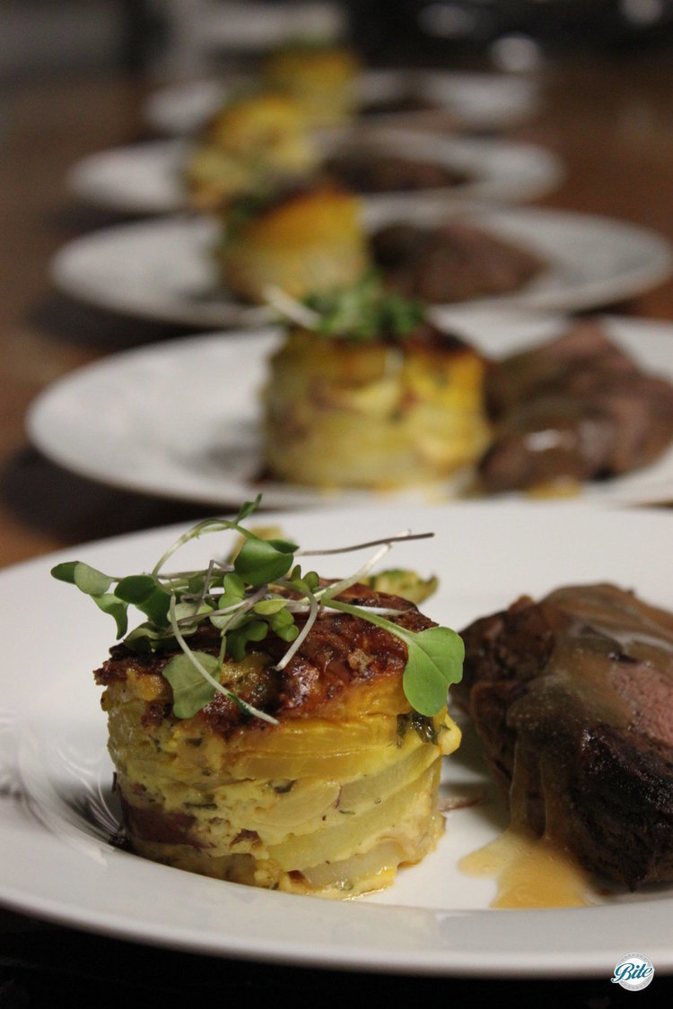 Plating lineup with potato gratin next to venison.