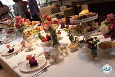 Vintage tea plates, tea sandwich assortment, scones, tea bread, hot tea with lemon, clotted cream and fresh preserves on high tea themed tablescape with garden roses