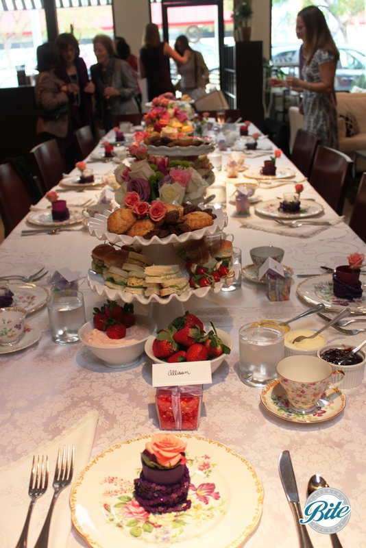 Table setting at high tea bridal shower with vintage linens and dishes. Stationary display of tea sandwiches, dessert assortment, fresh fruit and tea service