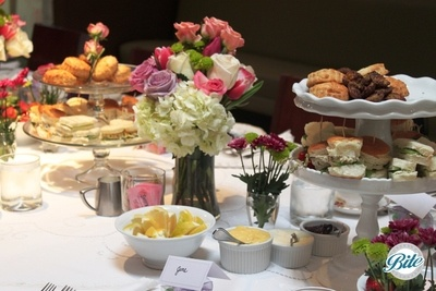 Detail shot of a bridal shower tea party display with assorted sandwiches, dessert, fresh flowers, scones, clotted cream, and hot tea