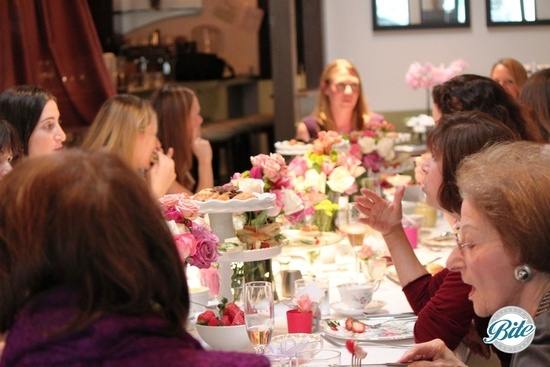 Guests seated for high tea. Tiered displays, vintage dishes and garden roses made a lovely display