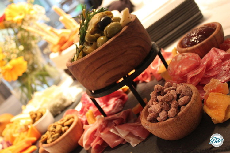 Closeup of antipasto plate with risers for olve bowl, salted nuts, quince, and assorted sliced meats