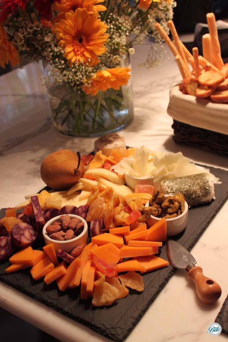 Overhead view of cheese display with sliced cheeses, nuts, and fruit. Background of flowers, breadsticks on marble countertop.