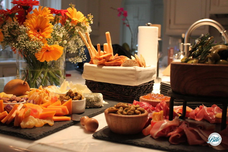 Cheese and charcuterie displayed on counter with breadsticks and flowers in the background
