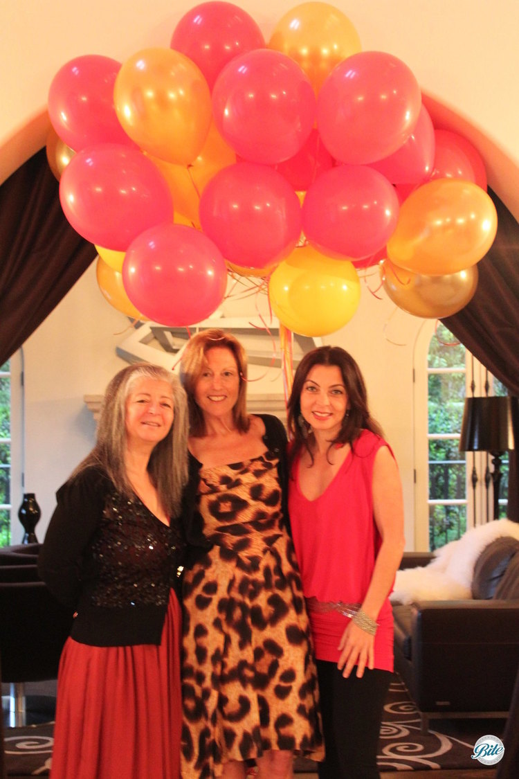 Lovely ladies posing with balloons for birthday party.
