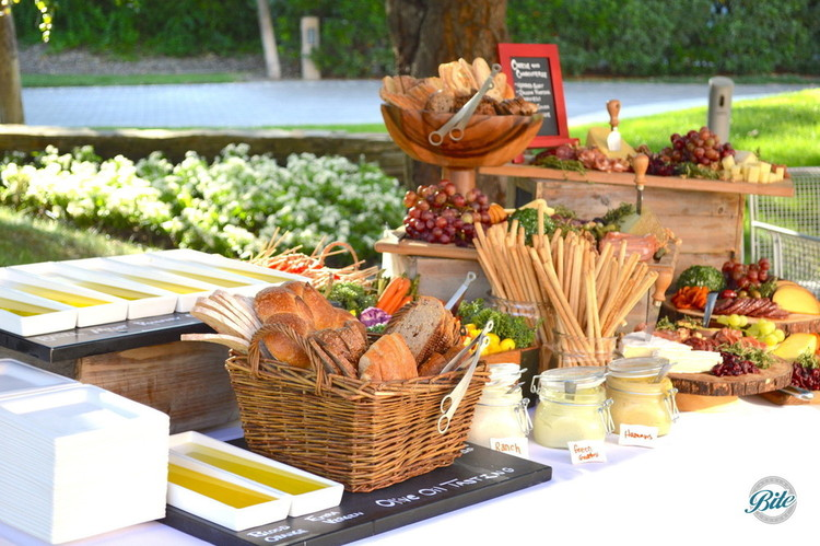 California olive oil station with artisan bread and breadsticks. Market crudite station also shown with assorted fruit and dressing