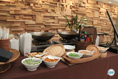 Asian noodle station with accompaniments featuring: edamame, scallions, and peanuts shown with bamboo, and wok, ready to serve guests
