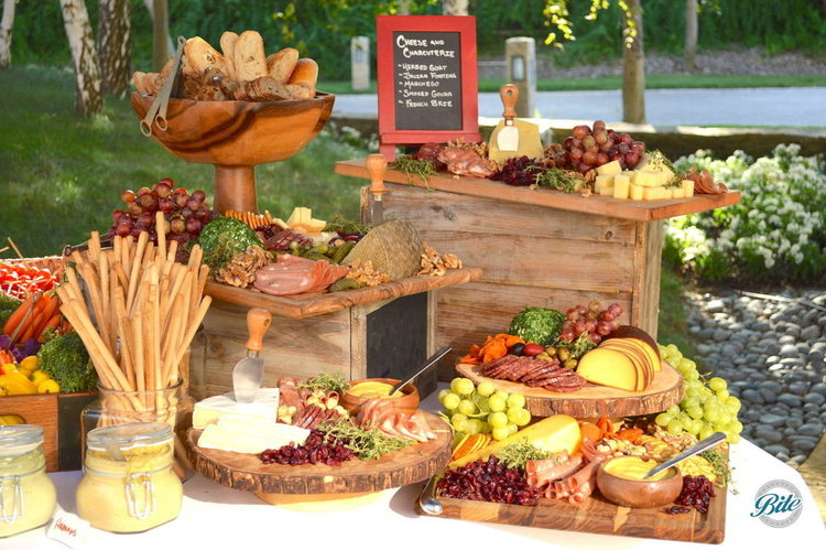 Cheese & Charcuterie Display against a beautiful outdoor backdrop. Fine meats, assortment of breads, grapes, mustards, etc on rustic display pieces