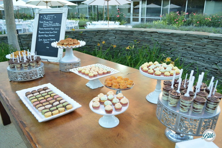Dessert Display with chocolate cake shooters, mini cupcakes, upside down cake bites with apples and cinnamon. Shown on porcelain and silver dishes for elegant presentation.