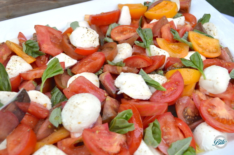Caprese Salad with heirloom tomatoes, mozzarella, basil, finished with seasoning and balsamic dressing