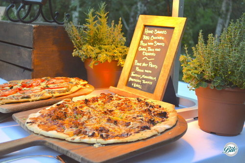 BBQ Chicken Pizza at grilled pizza station with fresh herbs and chalkboard menu.