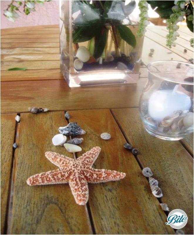 Table with candles, starfish, mussel and other shells