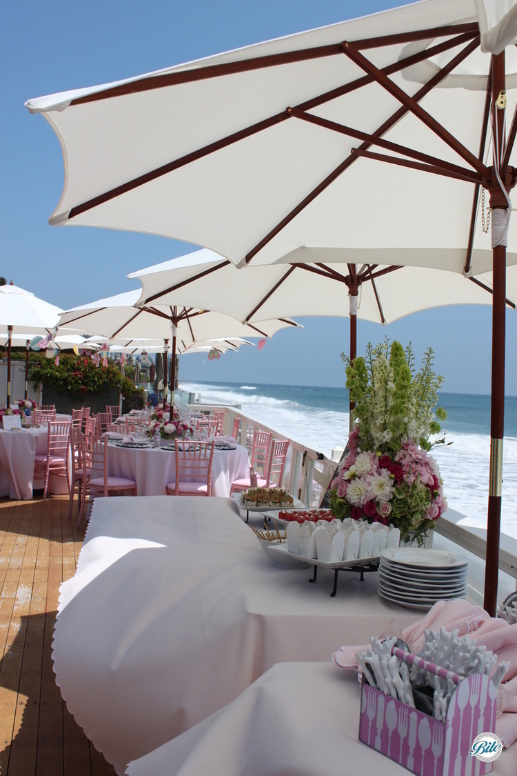 Pink themed baby shower buffet and tables over the water.