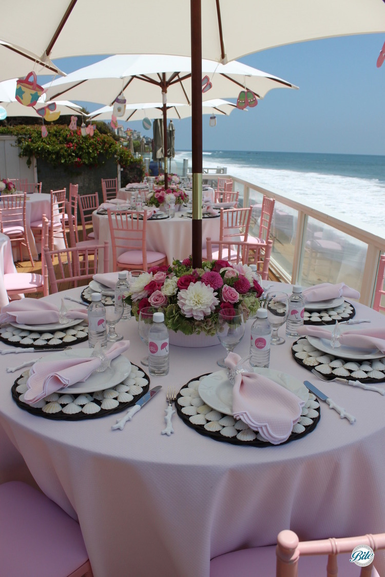 Tables set in pink with baby themed decor for baby shower/ gender reveal.