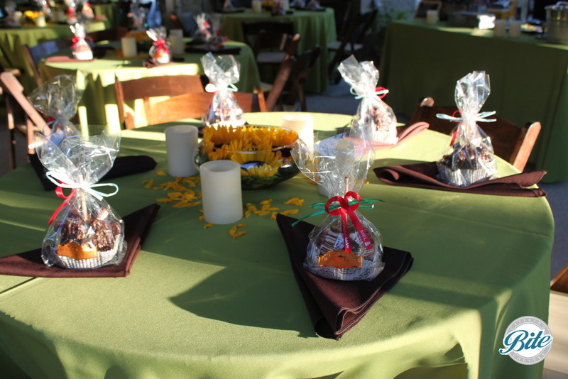 Green table linens with a sunflower display, candles, candied apples