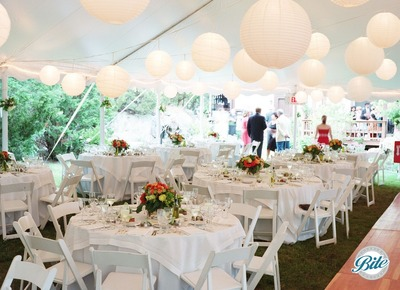 Outdoor tented wedding reception with plated dinner, fresh flowers, white linens and hanging paper lanterns