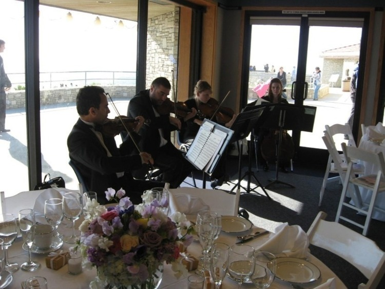 A live band playing in the sunset room with windows open to a beautiful day
