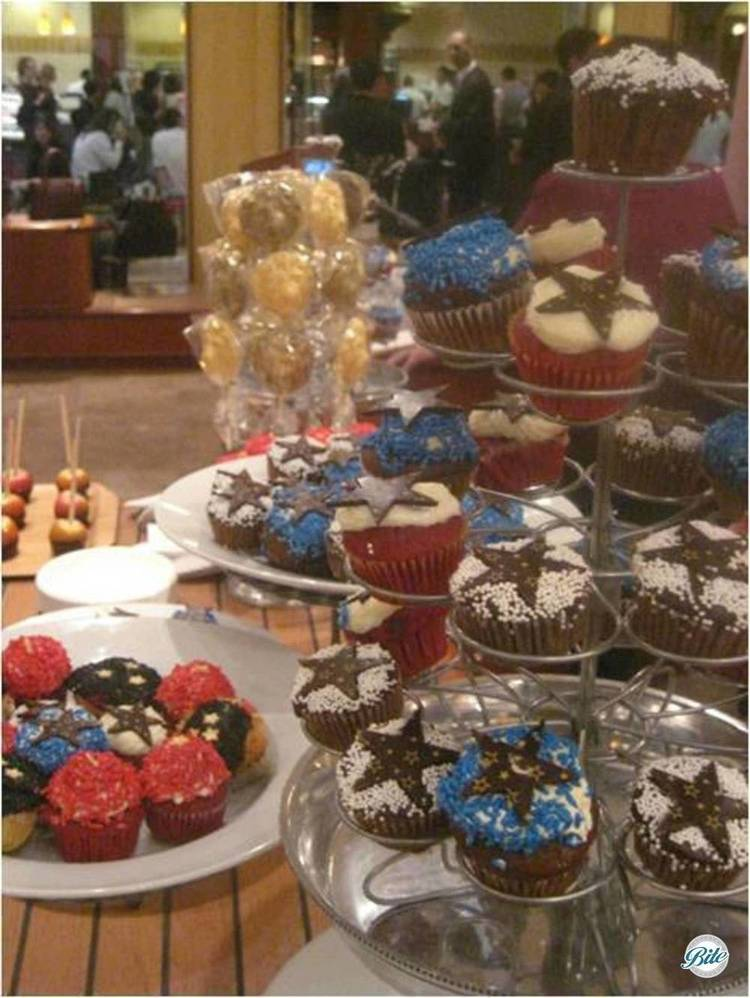 Chocolate cupcakes with star topper and caramel apples on dessert display.