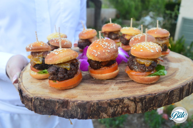 Mini BBQ Bacon Cheeseburgers served on brioche buns. Served on a polished tree tray.