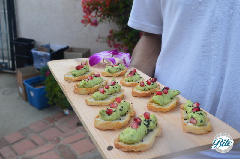 Edamame Hummus Crostini with Pomegranate Jewels. Tray passed on wood.