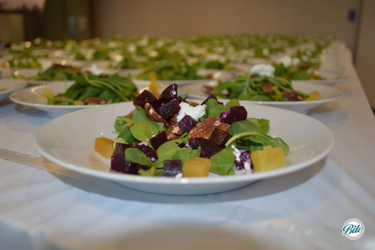 Plated salad with locally Sourced Roasted Autumn Red and Gold Beet Salad with goat cheese, arugula, toasted pecans and balsamic vinaigrette