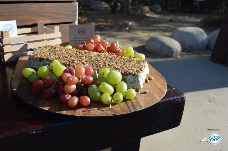 Grow Your Garden Crudité Display Closeup ofGorgonzola with Honey and Toasted Walnuts Savory Torta.  Displayed outdoors on a wooden display.