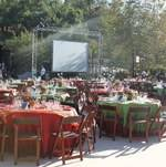 Tables and chairs set up in front of stage for outdoor fundraiser