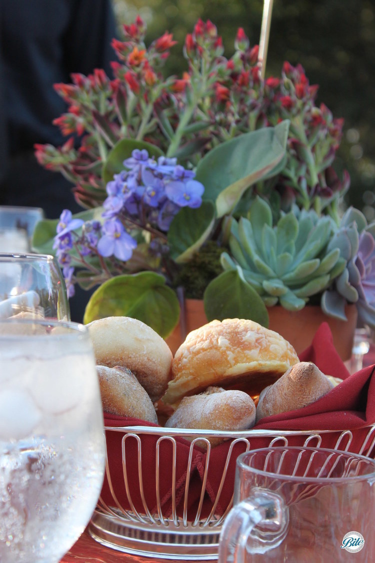 Basket of bread placed on table ahead of plated dinner