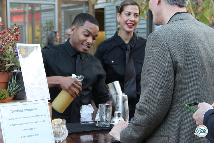 Happy attendees getting their signature cocktail at the bar station