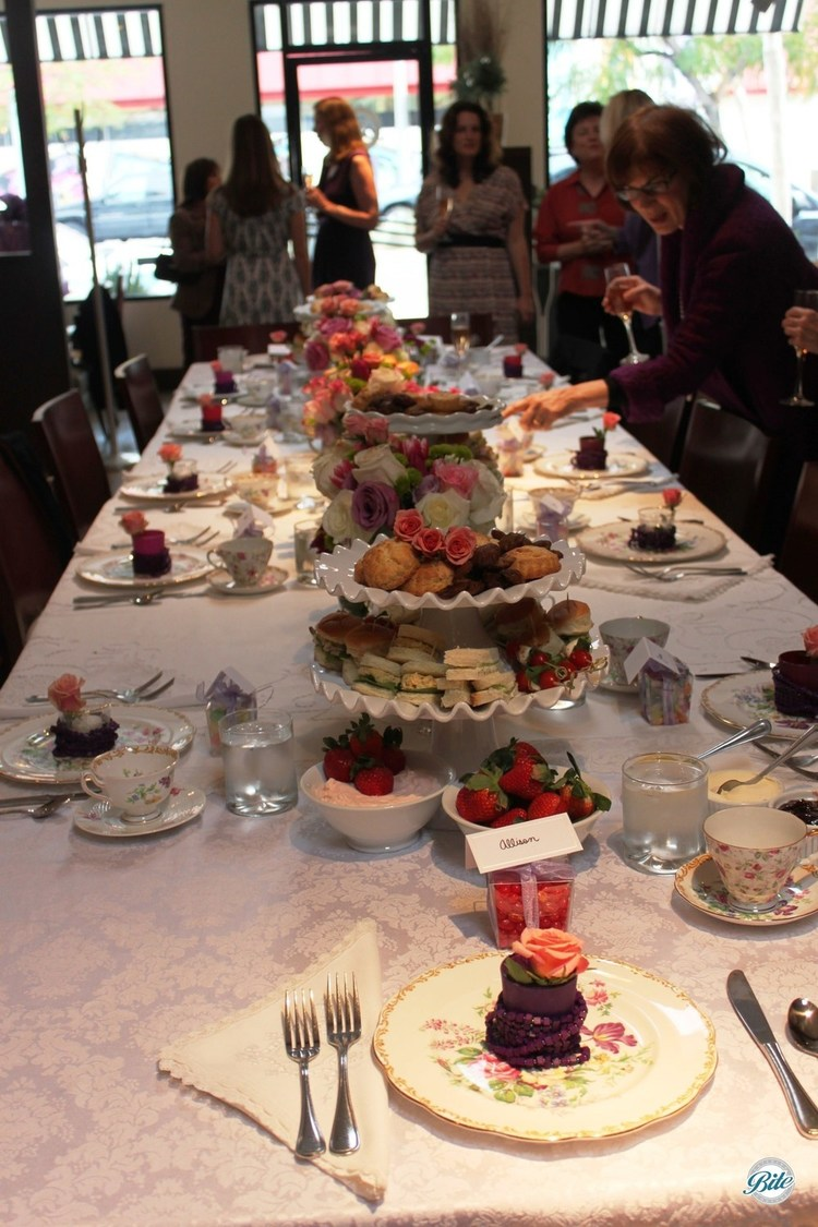 Elegant high tea reception with high tea spread, fresh flowers, garden decor, and vintage china