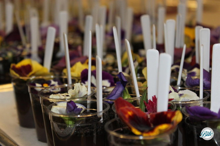 """""""Cup of Dirt"""" Chocolate Pot De Crème Dessert Shots with mini shovel spoons and edible flowers. Made for green event as part of a garden themed dessert display"""