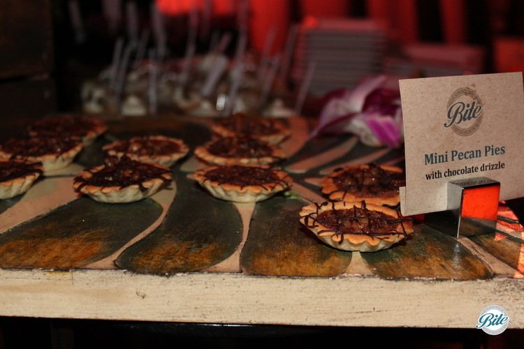 Mini Pecan Pies with chocolate drizzle.  Served on wooden display tray.