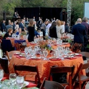 Fundraising dinner with tables, screen, and band
