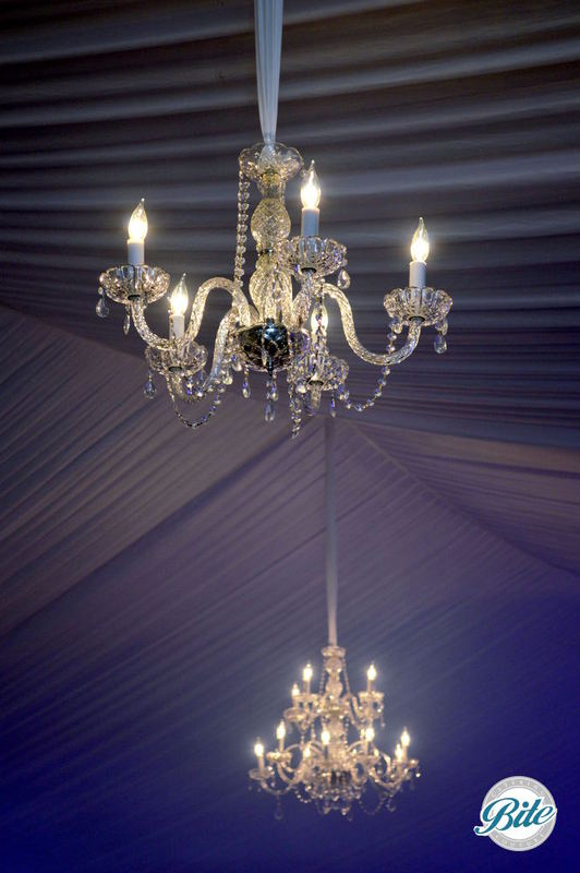 Crystal Chandeliers hang from the ceiling of the tent at the Alliance for the Arts gala