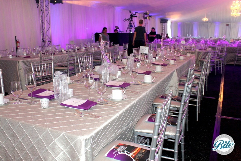 Elegant tablescape with chivari chairs, custom linen. and silver and purple accent colors.