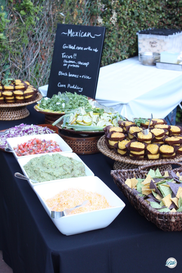 Outdoor wedding reception action station with grilled corn, corn pudding, black beans and rice, along with freshly made tacos