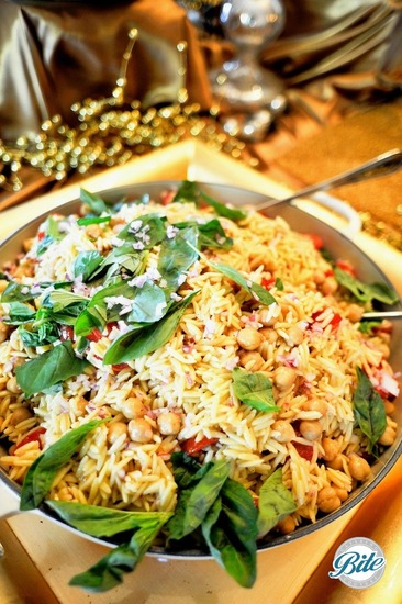 Orzo tossed with chickpeas, mint, basil and red wine vinaigrette, topped with fresh herbs, served family style