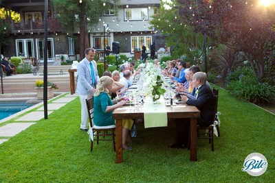 Backyard wedding reception plated dinner taking place outdoors on a long table