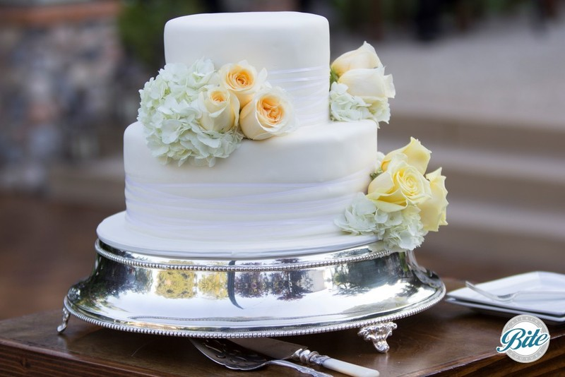Classic 2 - tier wedding cake with ivory icing and yellow flowers