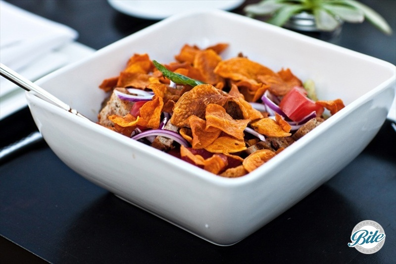 A Tuscan Summer favorite of Sun Ripened Rosa Tomatoes, Red onions, Capers and Torn Basil leaves Mixed with Olive CiabattaCroutons and Sweet Potato Crisps