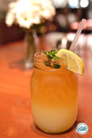 Arnold Palmer served in mason jar with fresh herb garnish