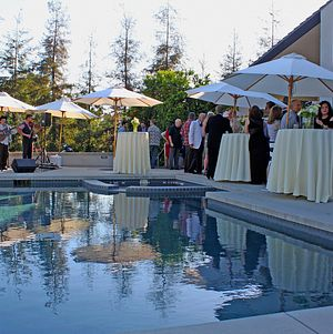 Cocktail hour guests enjoying bites and music by the pool